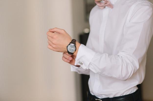 Préparation du matin du mariage. gros plan des mains du marié en chemise blanche, ajustant le poignet