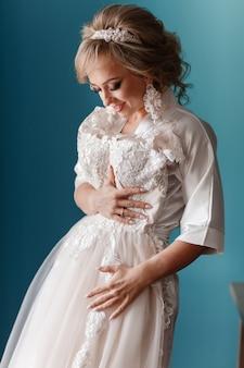 Préparation du matin de la mariée. heureuse belle jeune femme en peignoir de soie touchant sa robe de mariée en se tenant debout sur fond de mur bleu.