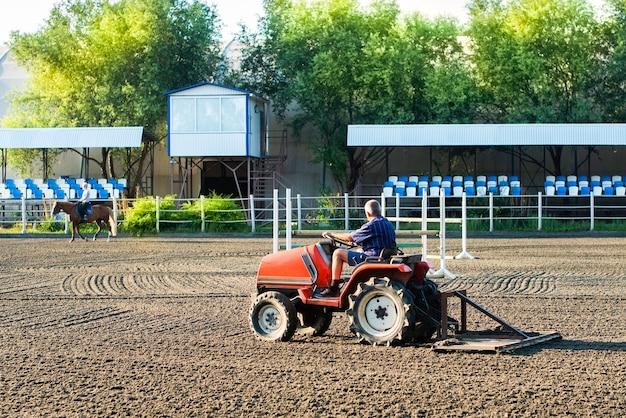 Préparation du parcours sur le circuit - le tracteur aligne le sol. un cavalier à cheval se promène à proximité. sports équestres, courses de chevaux, paris