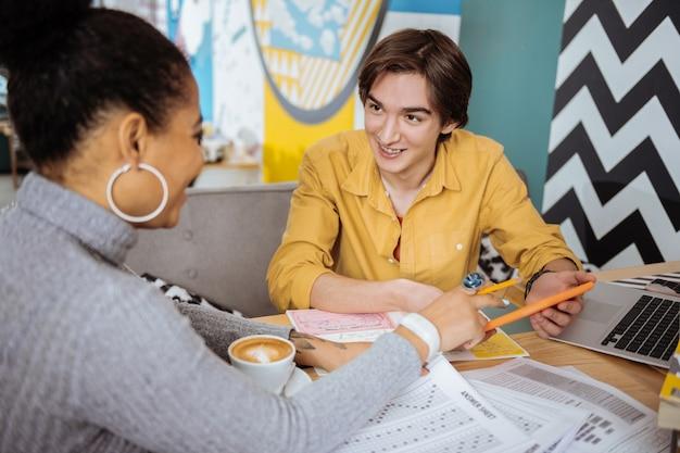 Préparation du projet de recherche. des étudiants buvant du café et discutant tout en faisant la tâche à domicile