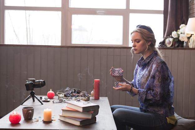 Préparation du rituel. agréable jolie jeune femme mélangeant des cartes de tarot tout en se préparant pour le rituel
