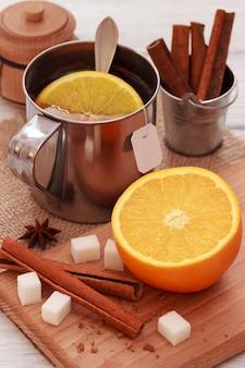 Préparation du thé noir dans une tasse métallique avec des bâtonnets de fruits orange et de cannelle