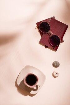 Préparation du voyage. passeports, lunettes de soleil, coquillages et une tasse de café sur fond rose à l'ombre des feuilles des arbres. tourisme local. vue de dessus et verticale