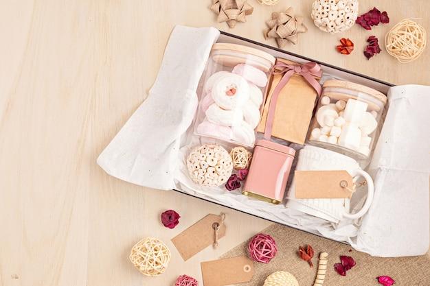 Préparation de l'emballage de soins et de la boîte-cadeau de saison avec boîte de guimauve, thé, café ou cacao et décoration de noël