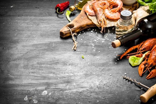 La préparation de fruits de mer frais. vin aux épices et crevettes fraîches, homard. sur un tableau noir.
