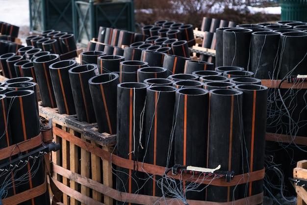 Préparation d'un grand feu d'artifice avec des tubes remplis de poudre à canon et de fil électrique au sol.