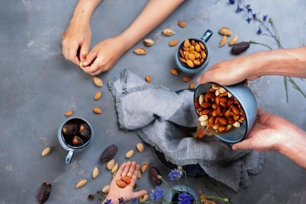 Préparation de lait d'amande maison. les mains des hommes tiennent un bol avec des graines d'amande