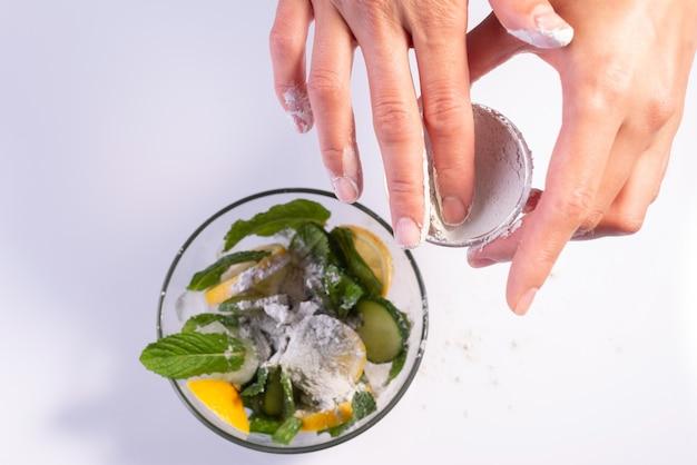 Préparation d'un masque cosmétique rafraîchissant mains de fille saupoudrant une salade d'ingrédients d'argile sur fond blanc.