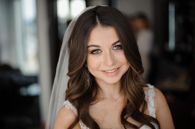 Préparation matinale de la mariée. belle et souriante mariée dans un voile blanc