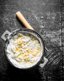 Préparation de pâte fraîche sur table rustique sombre.
