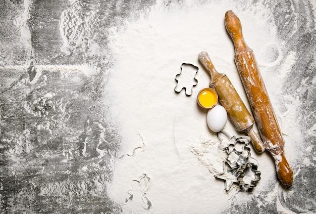 Préparation de la pâte ingrédients pour la pâte - œufs avec de la farine et des rouleaux à pâtisserie sur la table en pierre