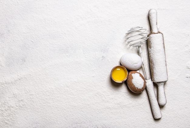 Préparation de la pâte. oeufs au venin et rouleau à pâtisserie dans la farine. espace libre pour le texte. vue de dessus
