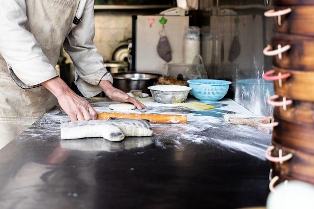 Préparation de la pâte à pain en boulangerie, des mains du boulanger, de la farine est versée, ce qui rend le dessert local du sichuan