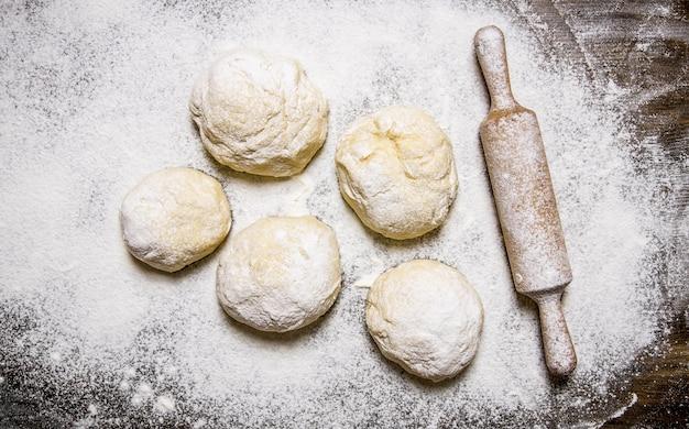 Préparation de la pâte. la pâte préparée avec de la farine et avec un rouleau à pâtisserie. sur une table en bois. vue de dessus