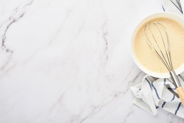 Préparation de la pâte pour les crêpes maison pour le petit déjeuner ou pour la maslenitsa. ingrédients sur la farine de blé de table, œufs, beurre, sucre, sel, lait