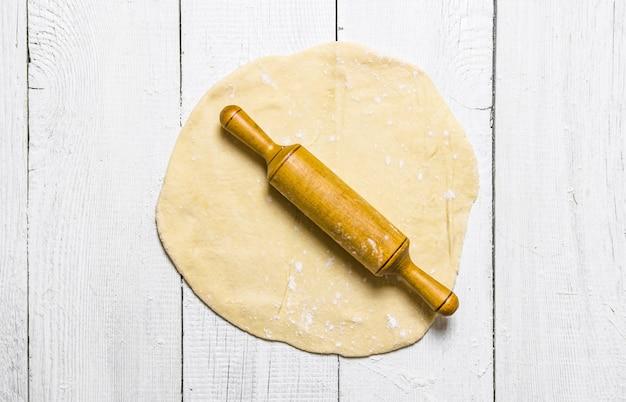Préparation de la pâte. prêt à rouler la pâte avec un rouleau à pâtisserie. sur un fond en bois blanc. vue de dessus