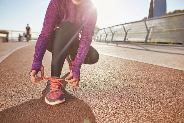 Préparation photo recadrée d'une femme mature active portant des vêtements de sport attachant ses lacets tout en