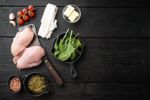 Préparation de poulet kiev à partir de poitrine de poulet farcie aux herbes, sur une table en bois noir