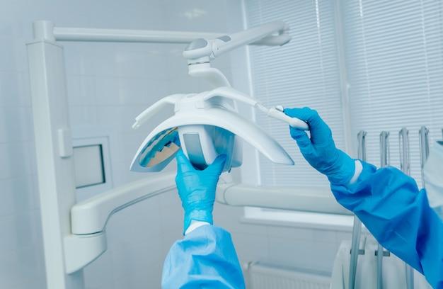 Préparation pour la chirurgie dentaire, fixation des poignées stériles au luminaire