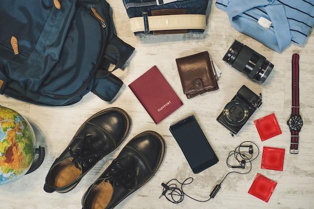 Préparation pour le concept d'activité de voyage en plein air, mise à plat. passeports à dos, portefeuille, téléphone et devises, chemise, appareil photo, passeport, préservatifs pour téléphone et autres accessoires de voyage collectés sur du parquet