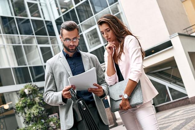 Préparation pour rencontrer deux jeunes gens d'affaires debout dehors dans la rue de la ville en train de lire
