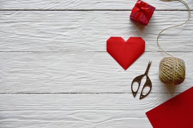 Préparation pour la saint valentin. feuille de papier rouge, ciseaux, coeur origami rouge, écheveau de ficelle et coffret cadeau sur un bois blanc.