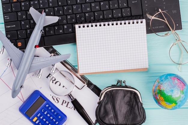 Préparation pour les vacances d'été. globe de calculatrice de portefeuille d'avion à plat sur le fond bleu. bloc-notes vierge au centre de la composition.