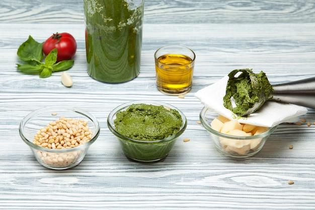 Préparation de sauce pesto au basilic et pignons de pin à l'aide d'un mixeur ingrédients frais bac de bois clair