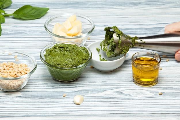 Préparation de sauce pesto au basilic et pignons de pin à l'aide d'un mixeur ingrédients frais