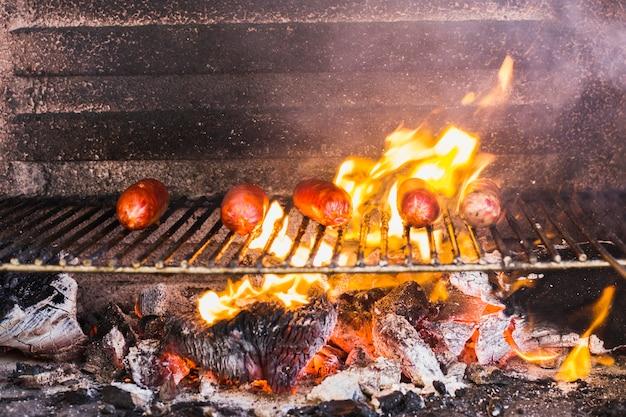 Préparation des saucisses sur la grille du barbecue