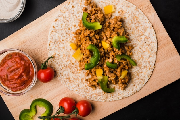 Préparation de tacos sur une planche à découper près de tomates et de sauce