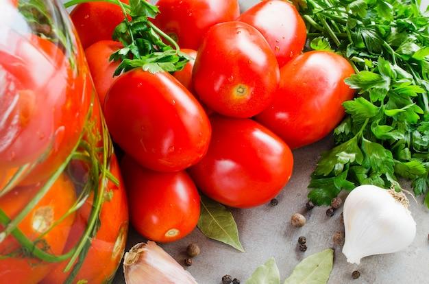 Préparation de tomates de conservation marinées avec des herbes, de l'ail, du sel et des épices.