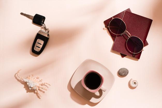 Préparation d'un voyage en voiture. passeports, lunettes de soleil, clés de voiture, coquillages et une tasse de café sur fond rose à l'ombre des feuilles des arbres. tourisme local. vue de dessus