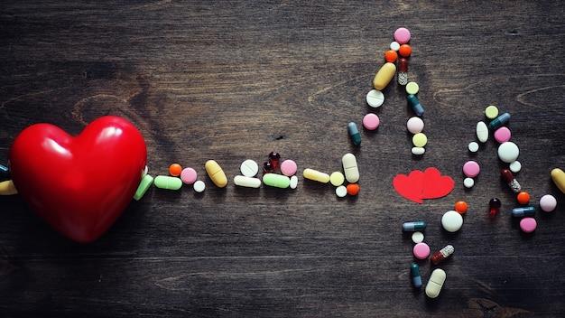 Préparations médicales pour le traitement des maladies cardiaques. le concept de dépendance à la santé cardiaque sur les comprimés. pilules et stéthoscope sur fond en bois.