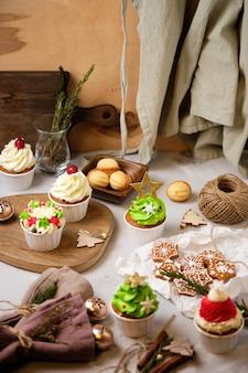 Préparer un cadeau de nouvel an pour des amis. bonbons pour noël. biscuits et cupcakes au pain d'épice du nouvel an avec crème au fromage à la crème et garniture au caramel.