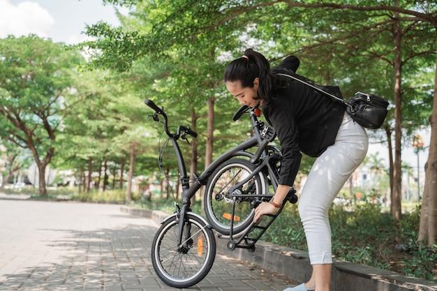 Préparer la femme travailleur essayant de plier son vélo pliant