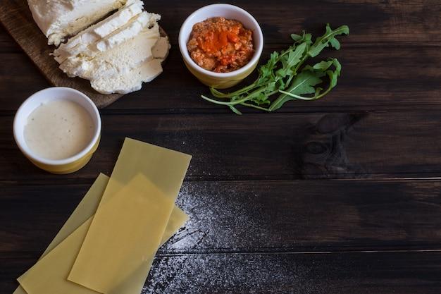 Préparer des lasagnes. pâte de lasagne crue, fromage mozarella, sauce bolognaise, sauce béchamel, un