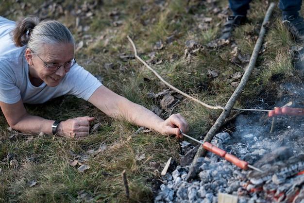 Préparer des saucisses sur le feu de camp