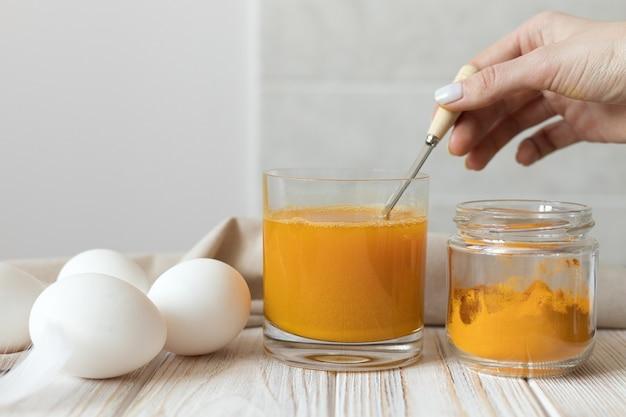 Préparer une solution de curcuma sec pour teindre les œufs de pâques. photo de haute qualité