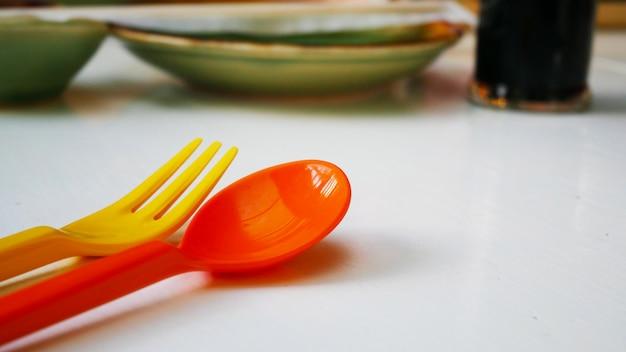 Préparez une cuillère orange et une fourchette jaune pour un enfant.