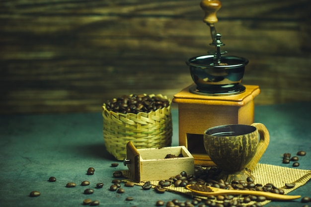 Préparez du café noir dans une tasse de noix de coco et un éclairage du matin. grains de café torréfiés dans un panier en bambou.