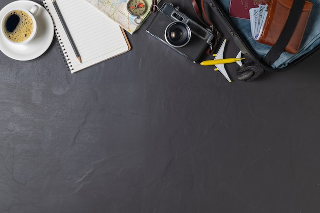 Préparez une valise, un appareil photo vintage, un cahier, une carte et du café noir sur le carrelage noir et copiez l'espace. concept de voyage