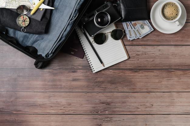 Préparez une valise, un appareil photo vintage, un cahier, une carte et du café noir sur du parquet et copiez l'espace. concept de voyage