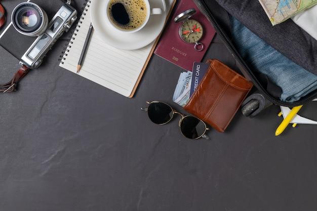 Préparez une valise, un appareil photo vintage, un cahier, un passeport, une carte et du café chaud sur le carrelage noir et copiez l'espace. concept de voyage