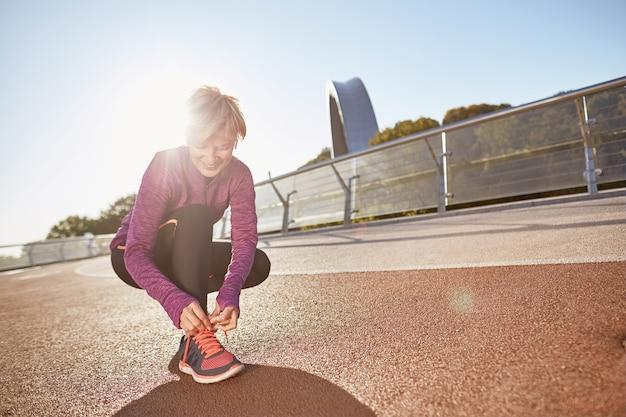 Préparez-vous à tirer sur toute la longueur d'une femme mature active portant des vêtements de sport attachant des lacets sur des vêtements de sport