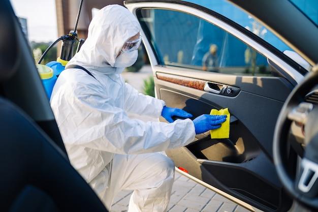 Le préposé au service de désinfection nettoie l'intérieur de la voiture