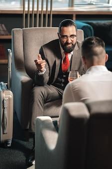 Près des bagages. homme barbu buvant du whisky assis sur un fauteuil près de ses bagages dans le hall de l'hôtel