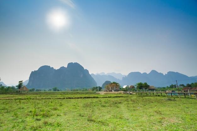 Prés et champs avec des montagnes au coucher du soleil, vang vieng, laos