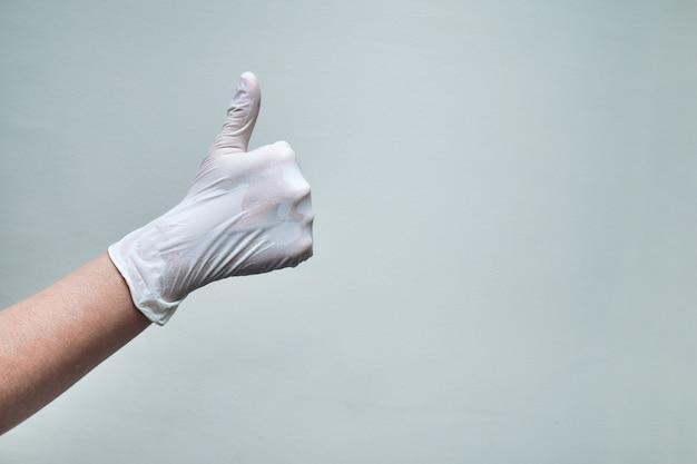 Près de la main avec un gant faisant les pouces vers le haut avec espace de copie.