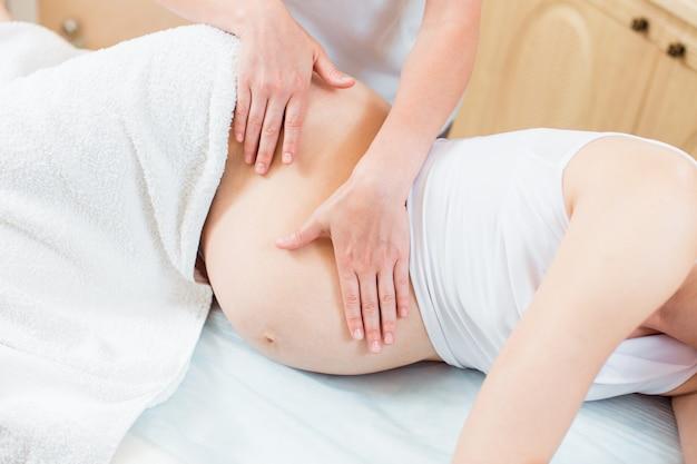 Près des mains féminines d'un massothérapeute fait un léger massage sur le ventre d'une fille enceinte dans une salle de cosmétologie